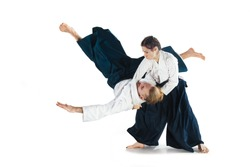 Man and woman fighting at Aikido training in martial arts school. Healthy lifestyle and sports concept. Man with beard in white kimono on white background. Karate woman with a concentrated face.