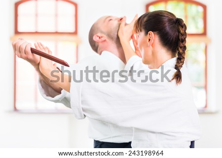 Man and woman fighting with wooden knifes at Aikido training in martial arts school  Stock photo ©