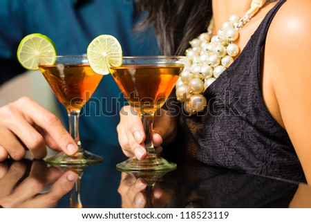 Man and woman flirting intimately at bar drinking cocktails