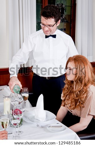 man and woman for dinner in restaurant waiter serving mineral water