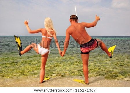 man and woman go to diving on summer beach
