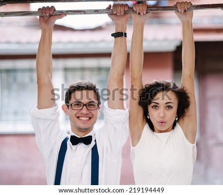 Man and woman hanging with hands on a bar. Classic clothes.