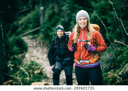 Man and woman happy couple hikers trekking in green autumn forest and mountains. Young people walking on trail with backpacks, healthy lifestyle adventure, camping on hiking trip, vintage photo style.