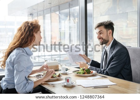 Man and woman having business lunch at restaurant sitting at table near window eating fresh salad drinking coffee discussing project smiling cheerful