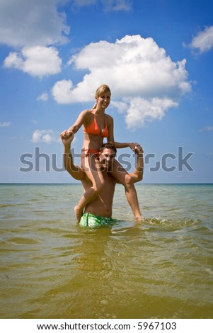Man and woman having good time on a beach, man carrying woman on his shoulders