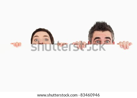 Man and woman hiding behind a copy space against a white background