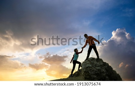 Man and woman hikers helping each other to climb a big stone at sunset in mountains. Couple climbing on a high rock in evening nature. Tourism, traveling and healthy lifestyle concept. Photo stock ©