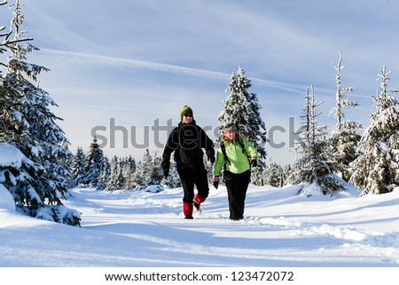 Man and woman hikers walking in winter mountains. Young couple happy walking no white snow in mountain forest, Poland