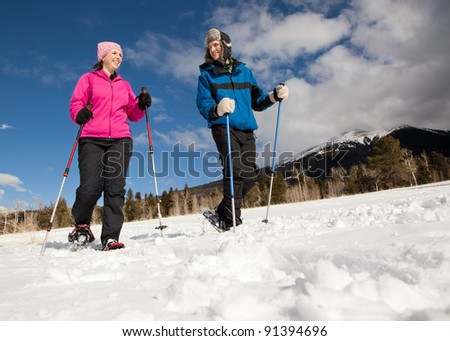 Man and Woman Hiking in Snowshoes