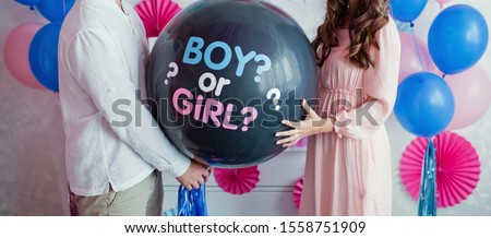 man and woman holding black balloon with 'boy or girl?' on gender reveal party Stockfoto ©