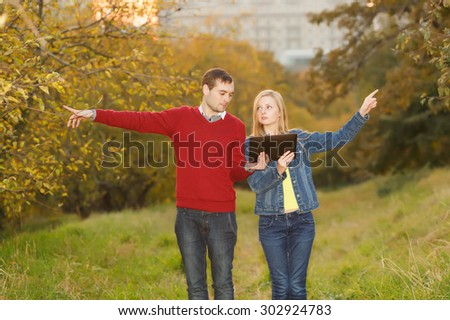 Man and woman holding electronic tablet in hands, argue where to go. Point the finger in different directions. Young students. September, October, golden autumn. Traveler, tourist, navigator, lose.