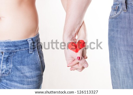Man and woman holding hands and making red heart