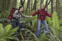 Man and woman holding hands and walking with backpacks in the forest