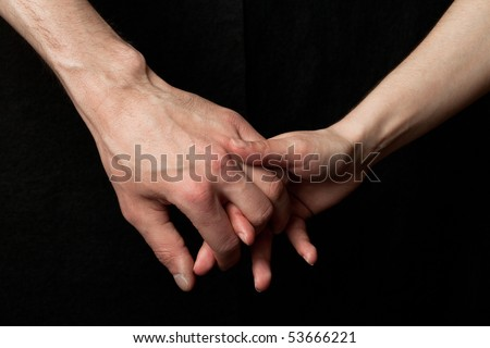 Man and woman holding hands, on black background
