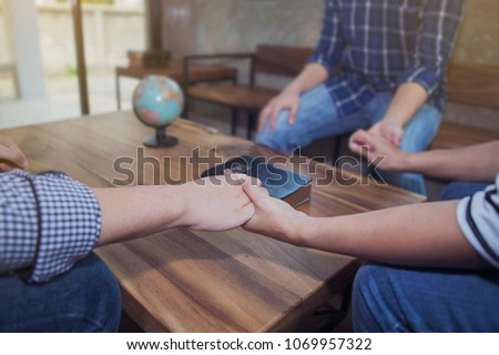 man and woman holding hands prays together around wooden table with blurred bible and world globe, Christian concept, pray for world peace