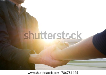 man and woman holding hands to...