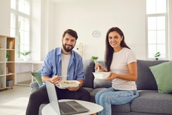 Man and woman holding takeaway food trays and having lunch at home sitting on sofa in front of laptop. Happy couple having fun at home on the weekend. Eating and people concept.