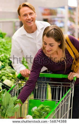 Man and woman in a supermarket at the vegetable shelf shopping for groceries, she is putting some stuff into the shopping cart