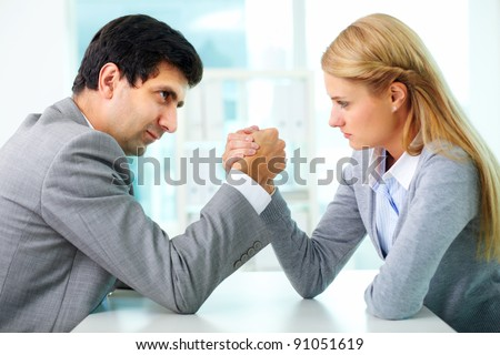 Man and woman in arm wrestling gesture on working table during meeting