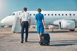Man and woman in aviation uniform are walking to plane stairway with luggage before departure