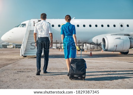 Man and woman in aviation uniform are walking to plane stairway with luggage before departure Сток-фото ©