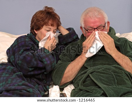 Man and woman in bed blowing noses