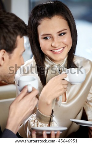 Man and woman in cafe drink coffee and smile, looking against each other