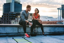 Man and woman in fitness clothes relaxing on the rooftop during workout. Fitness couple taking a break during workout sitting together on the fence of a terrace and talking.