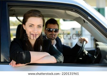 Man and woman in his car stops at petrol station