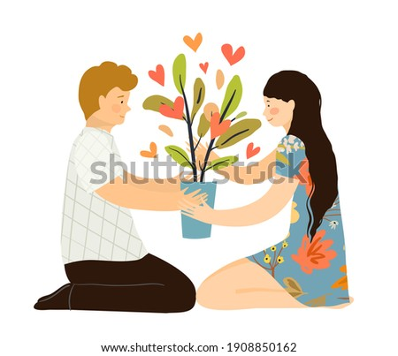 Man and woman in love sitting with houseplant on the floor, hunker down, holding flowerpot with bearing hearts plant. Growing love together psychological concept.  Stockfoto ©