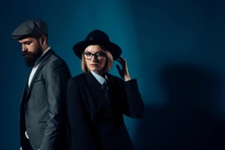 Man and woman in oldfashioned suit and hat on dark background. Couple of detectives or researchers, private investigators. Couple in love or work partners working together. Retro detective concept.