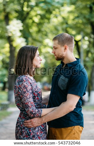 Man and woman in summer clothes look at each other seriously while they hug #543732046