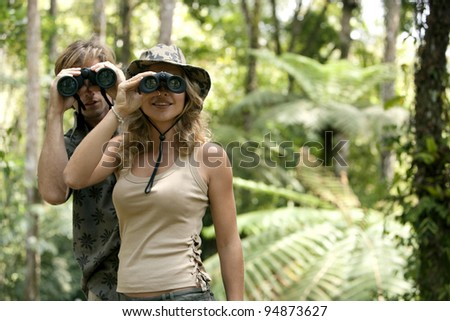 Man and woman in the forest looking at the camera through binoculars.