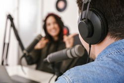 Man and woman in white shirts podcasters interview each other for radio podcast