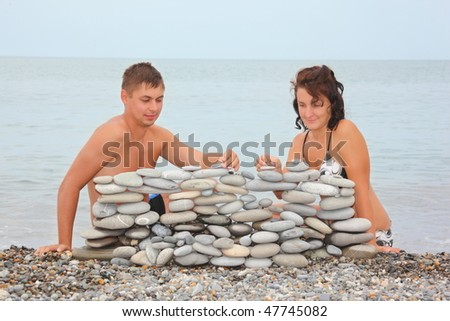 man and woman is building construction of pebbles near water.
