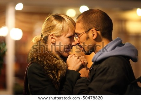 man and woman is cuddling in coldly nightly fall city. focus on woman's face.
