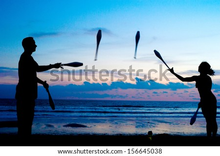 Man and woman juggling on the ocean beach at sunset. Bali, Indonesia