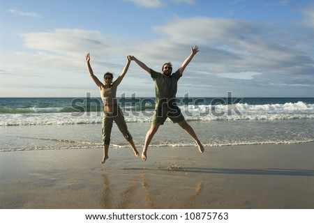 Man and woman jumping in a sunny beach