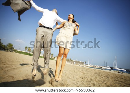 Man and woman jumping on beach