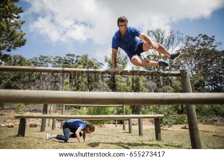 Man and woman jumping over the hurdles during obstacle course in boot camp #655273417