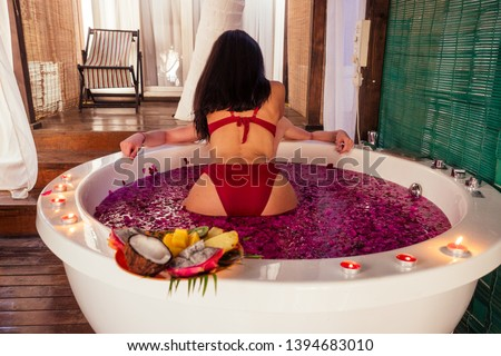 man and woman kissing and hugging romantic fruits, candles and champagne.sex in the water