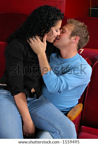 Man and woman kissing in back row of movie theater