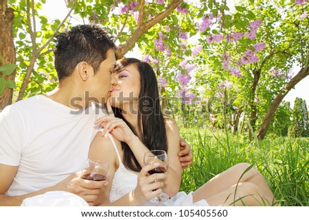 Man and woman kissing under the lilac bush