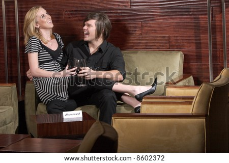 Man and Woman laugh during a conversation at a wine lounge