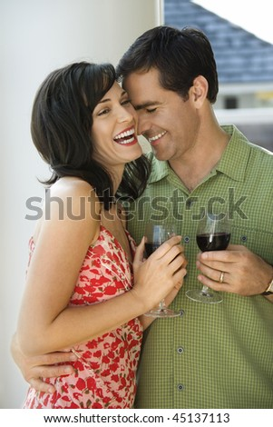 Man and woman laugh while standing with glasses of wine. Vertical shot.