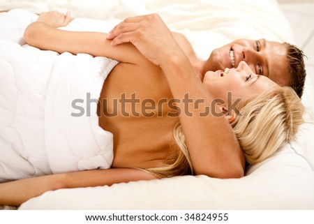 man and woman laying in bed smiling at camera