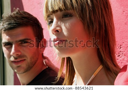 Man and woman leaning against a wall