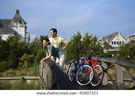 Man and woman leaning and relaxing on a bridge railing with their bikes. Horizontal shot. - stock photo