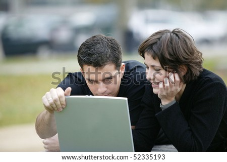 Man and woman lying in front of a laptop computer