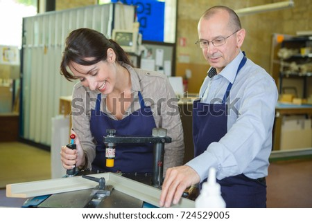 Man and woman making picture frame